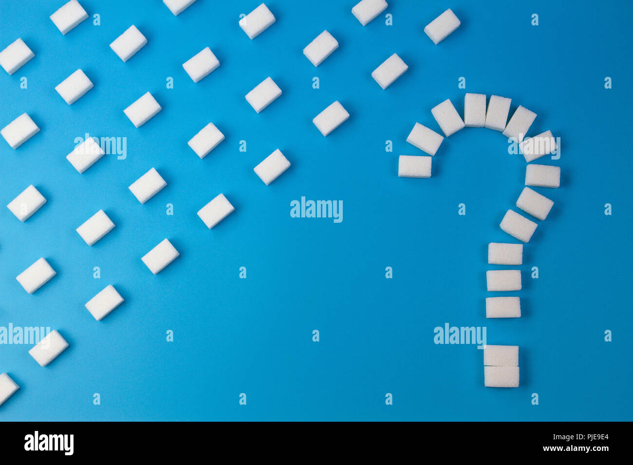 Sugar cubes shaped as a question mark sign on blue background. - Stock Image