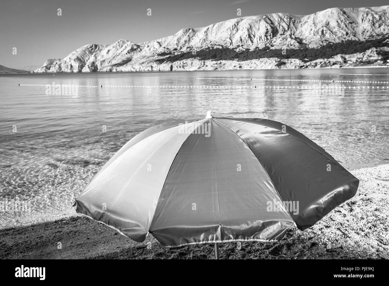 A lone umbrella on the beach at daybreak at the waters edge of the Adriatic at Baska on the island of Krk in Croatia - Stock Image