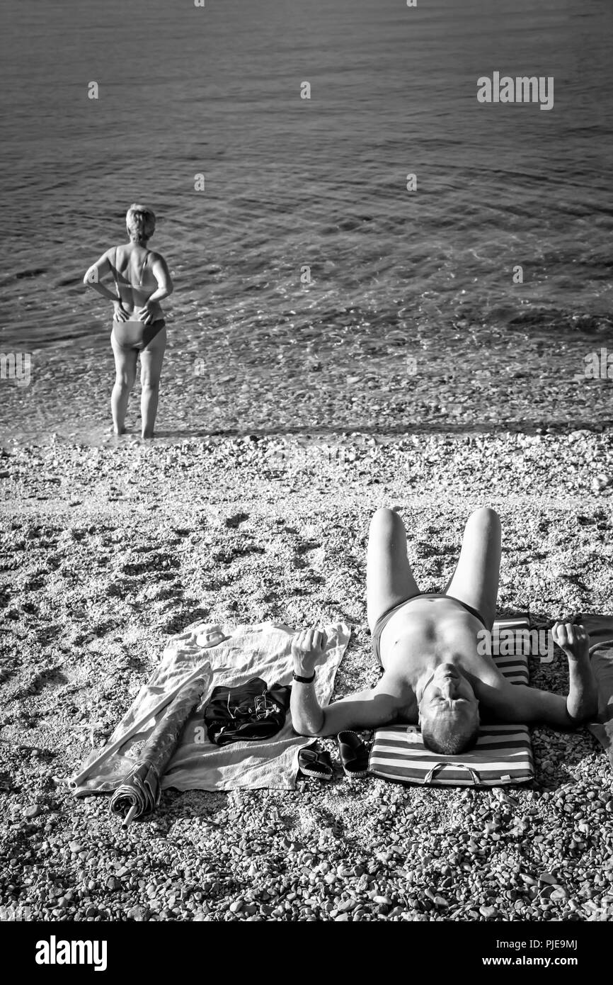 A woman at water's edge stares out over the Adriatic on the Croatian island of Krk at the resort of Baska, while man sunbathes on beach Stock Photo