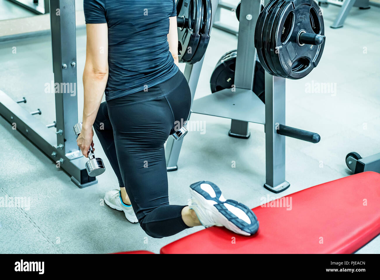 Young woman does leg lunge exercises in gym Stock Photo
