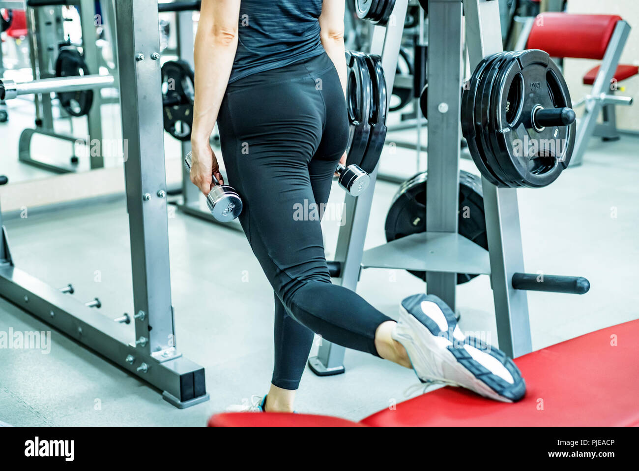 Young woman does leg lunge exercises in gym - Stock Image