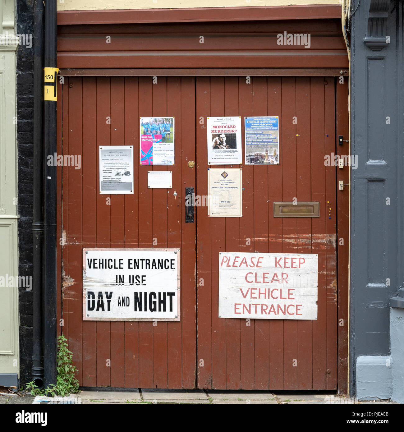 Posters and flyers pinned on brown painted doors - Stock Image
