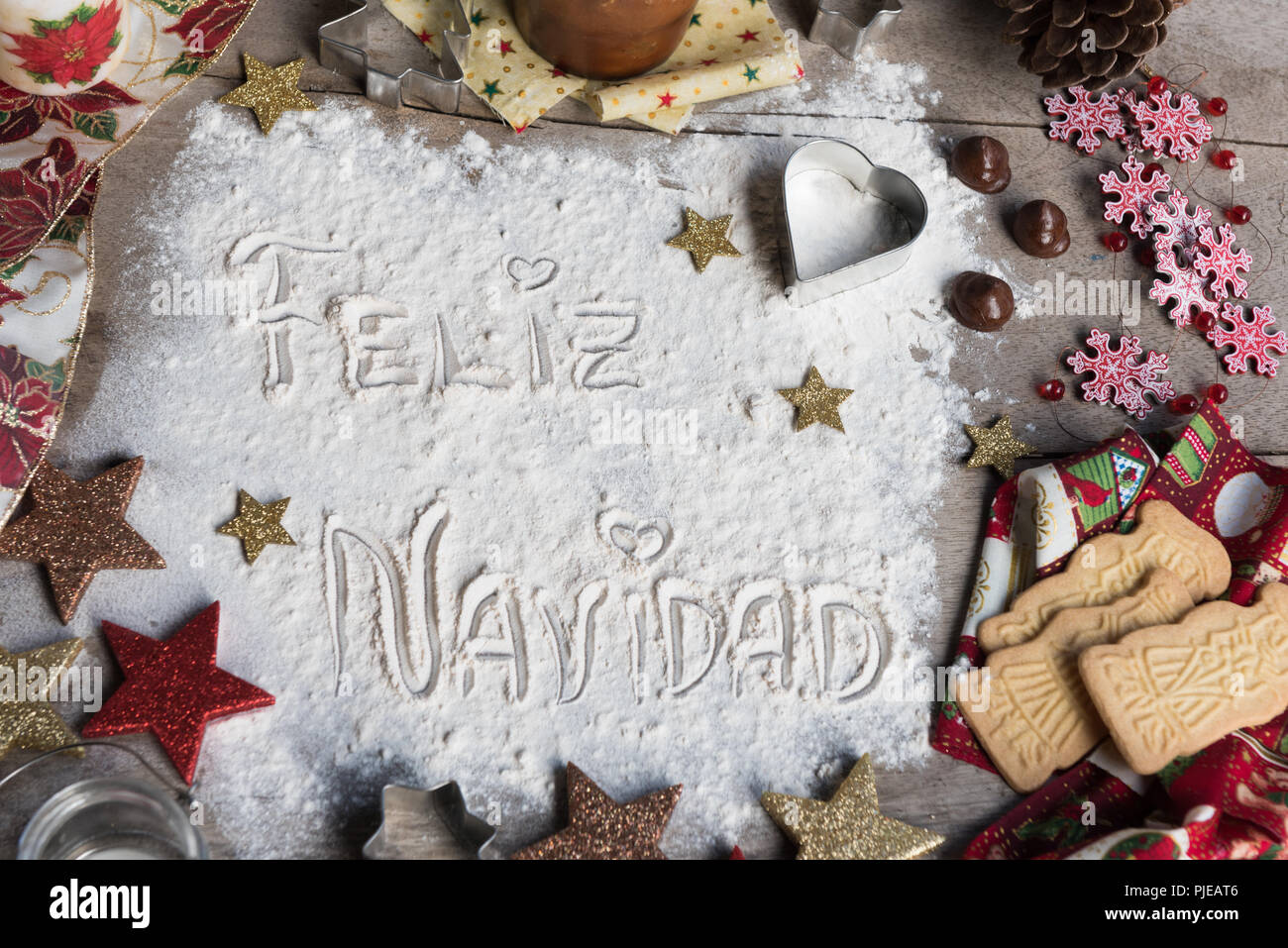 feliz navidad spanish text made with flour surrounded by christmas decorations seasonal concept
