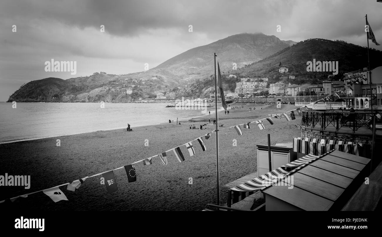 LEVANTE ITALY - APRIL 24 2011; Mediterranean seaside beach  village set below hill with characteristic building  with people on beach surrounded by hi - Stock Image