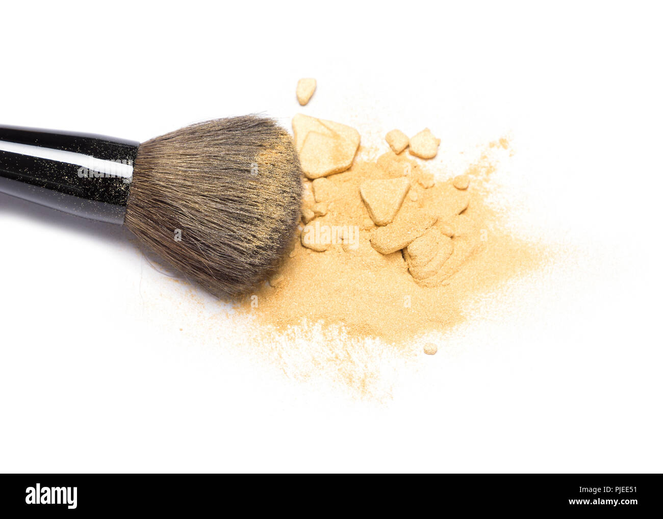 Close-up of makeup brush with crushed mineral shimmer powder golden color on white background - Stock Image