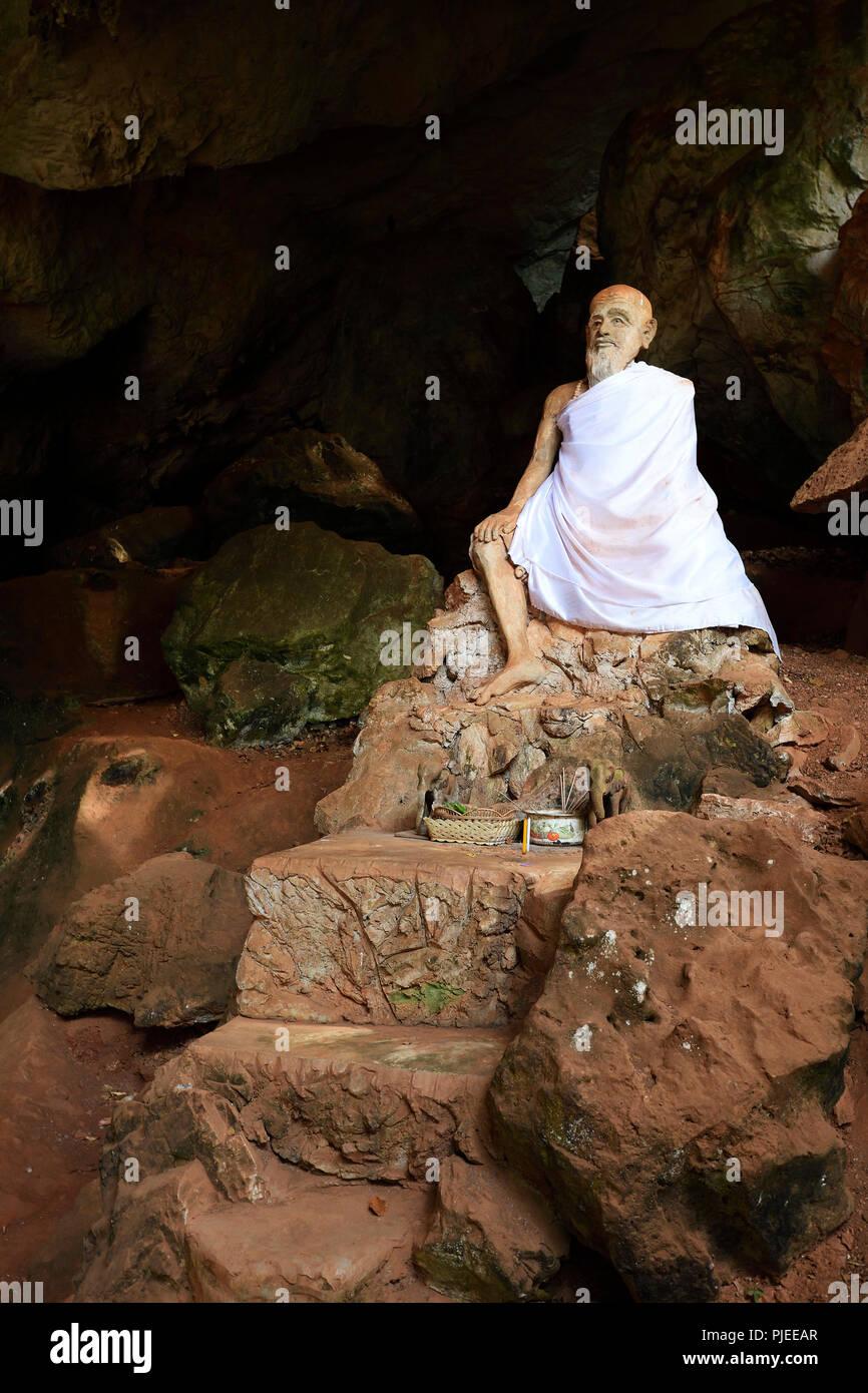 seated statue of a monk in the cave temple Wat Tham Suwan Khuha, Phang Nga, Thailand, sitzende Statue eines Mönch im  Höhlentempel Wat Tham Suwan Khuh - Stock Image