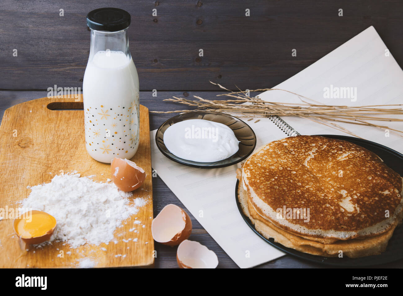 fresh, hot pancakes in a frying pan, eggs, milk, flour on a wooden table - Stock Image