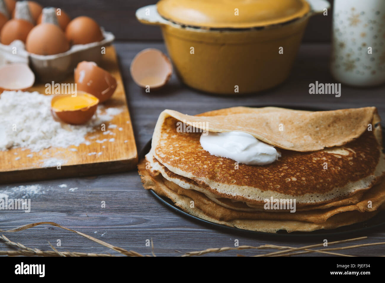 fresh, hot pancakes in a frying pan, eggs, milk, flour on a wooden table. Top view - Stock Image
