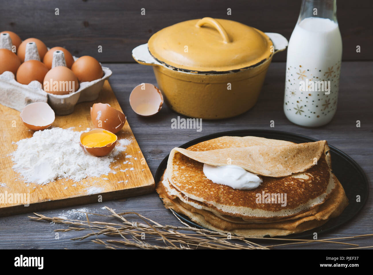 fresh, hot pancakes in a frying pan, eggs, milk, flour on a wooden table. - Stock Image