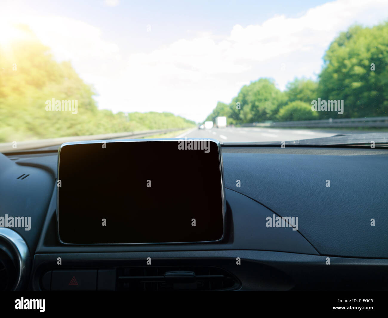 Car Interior with Navigation system and German Autobahn in background - Stock Image