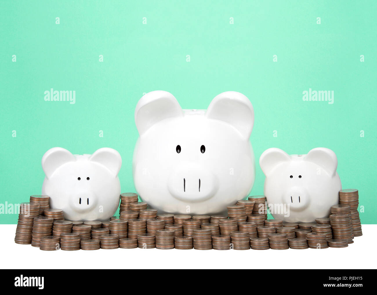 Three Piggy Banks In A Row One Large Two Small Behind A Wall