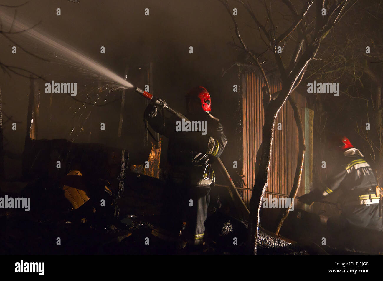 Firefighters extinguish the house. Night, it's snowing. - Stock Image