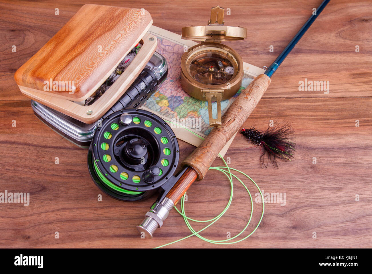 fly fishing rod with a coil and flies lie on old, wooden boards Stock Photo