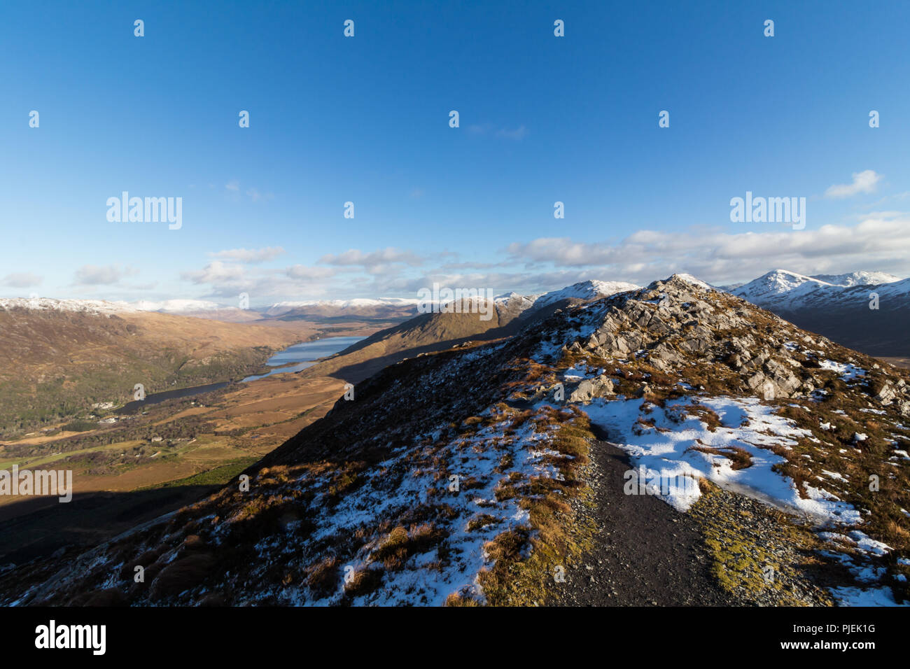 Summit of Diamond Hill in Connemara National Park in winter overlooking Kylemore Abbey and Kylemore Lough on left and the snowcapped Twelve Bens. - Stock Image