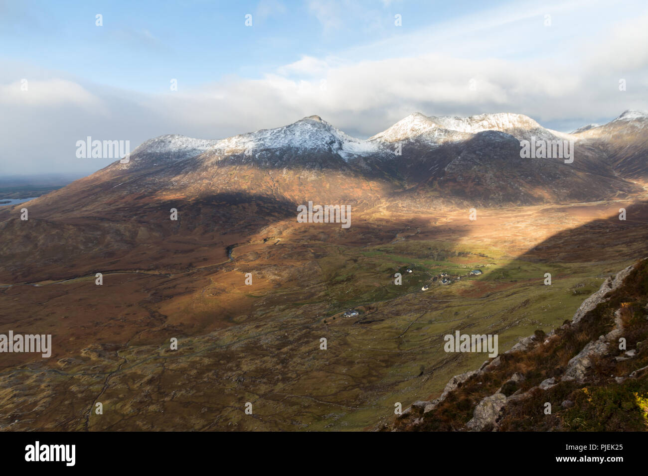 Sunlight and shadow on The Twelve Bens mountains in winter, Connemara, County Galway, Ireland. - Stock Image