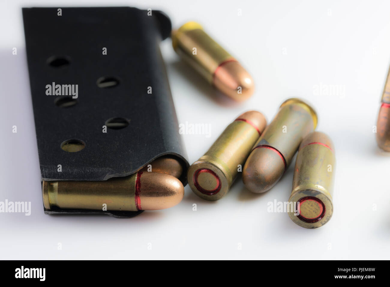 Close up of 22mm caliber bullets in a black gun clip isolated on white. - Stock Image