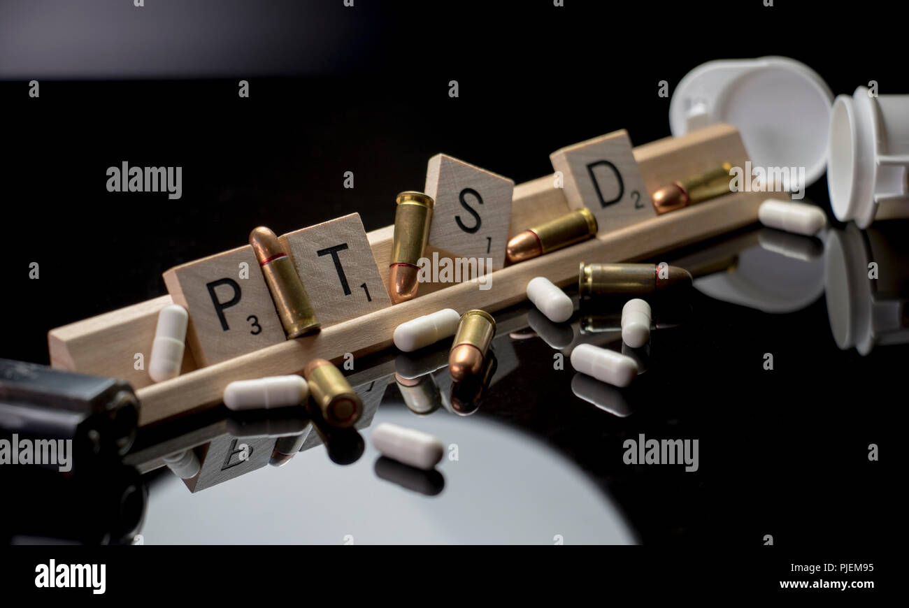 PTSD concept with Scrabble text blocks, bullets, pills, hand gun and pill bottle. - Stock Image