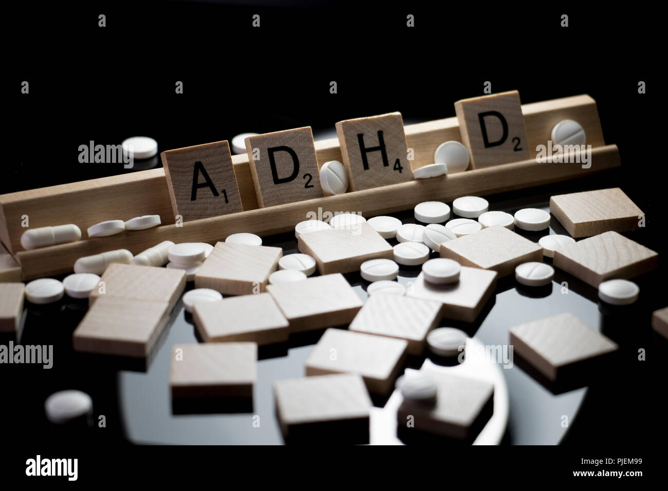 ADHD spelled in Scrabble text with white prescription pills spilled on a black table. Concept of Attention Deficit Hyperactivity Disorder medication - Stock Image