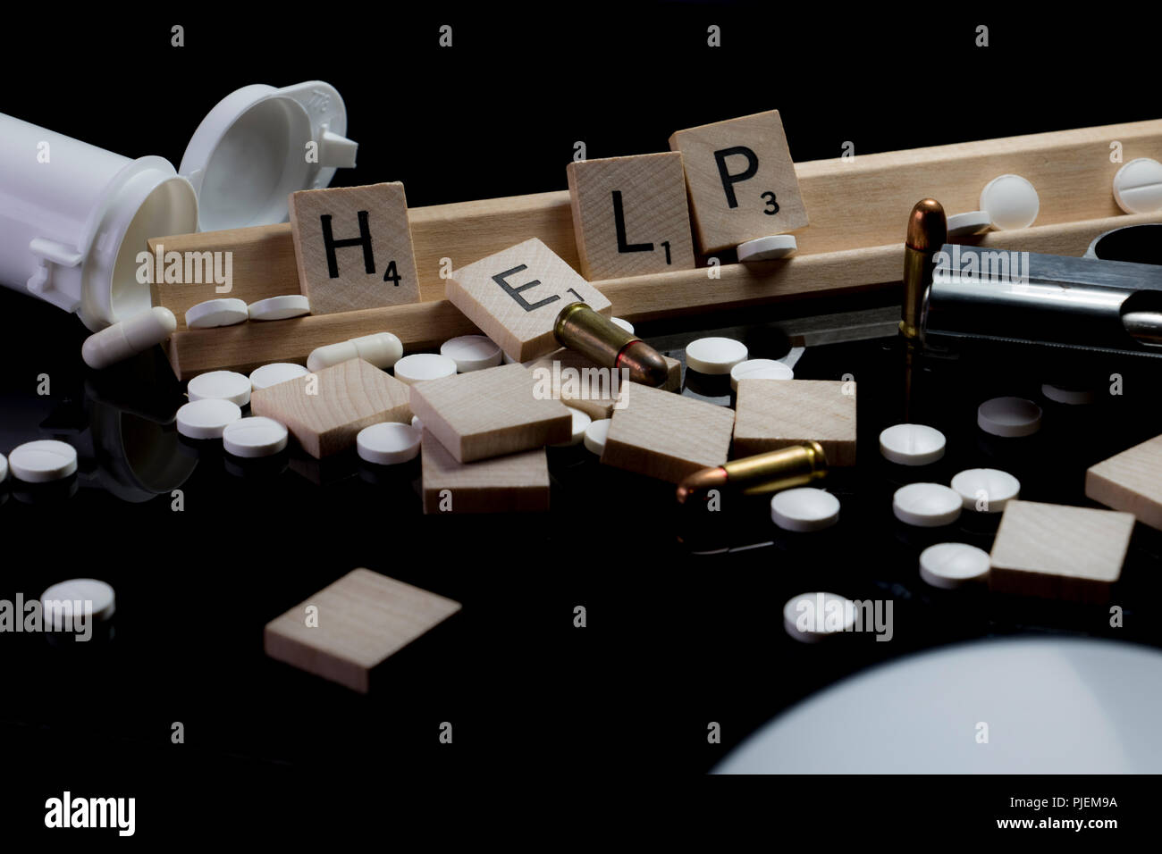 HELP spelled in block text letters with pills, bullets, pistol and pill bottle. Crisis prevention concept. - Stock Image