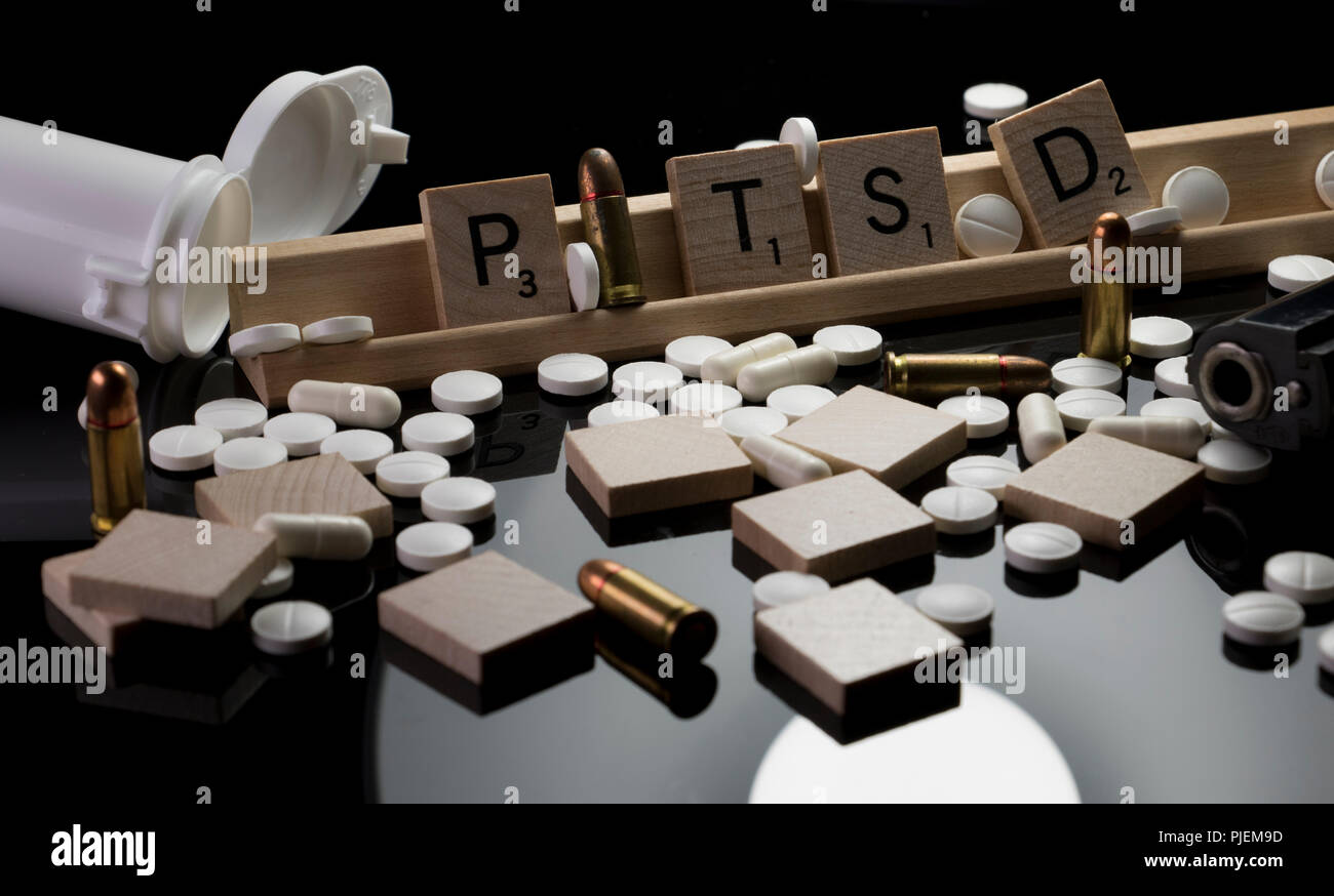 PTSD in Scrabble text with pills, bullets and hand gun. Concept of Post Traumatic Stress Disorder with opened bottle of antidepressants, ammunition - Stock Image