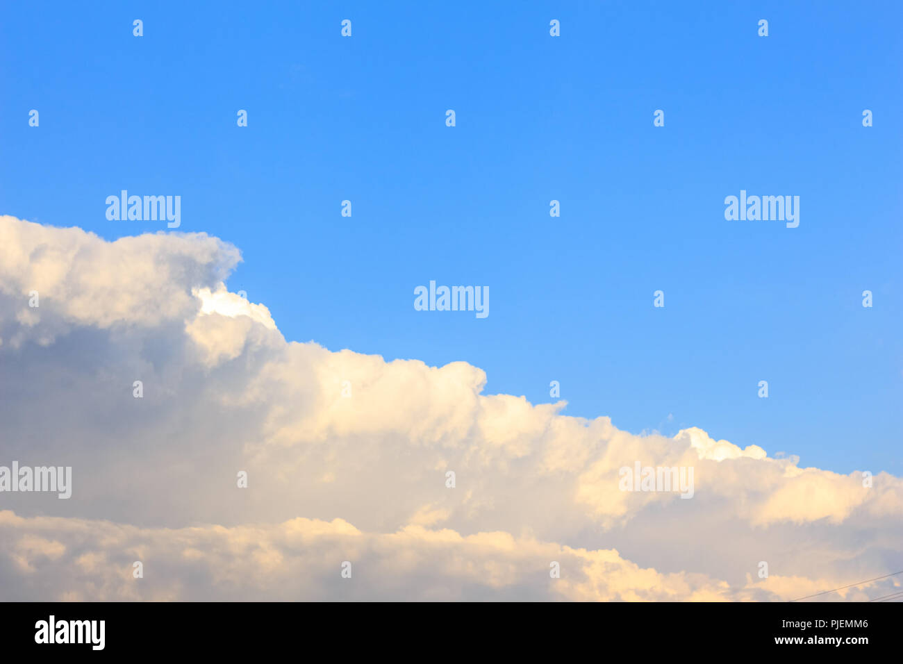 Beautiful sky background with white bright cumulus clouds and blue sky - Stock Image