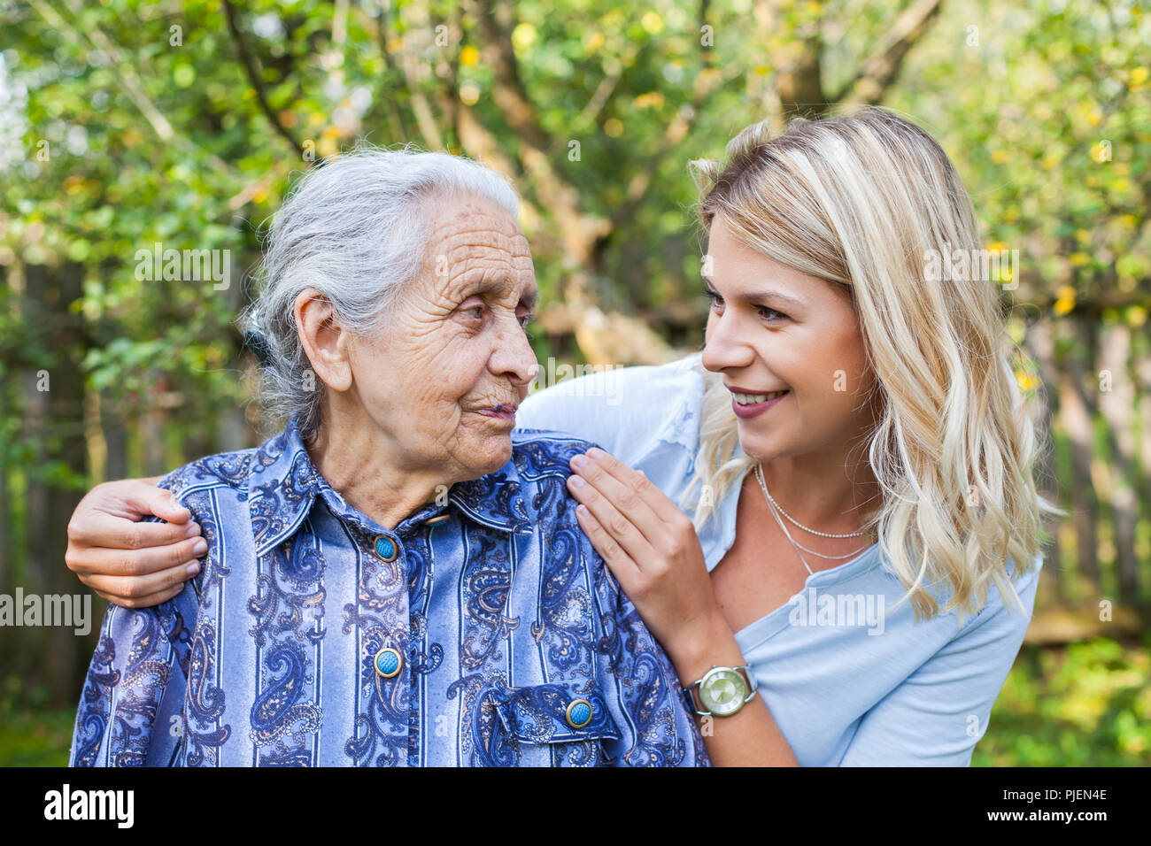 Smiling young caretaker walking with senior lady in the garden - Stock Image