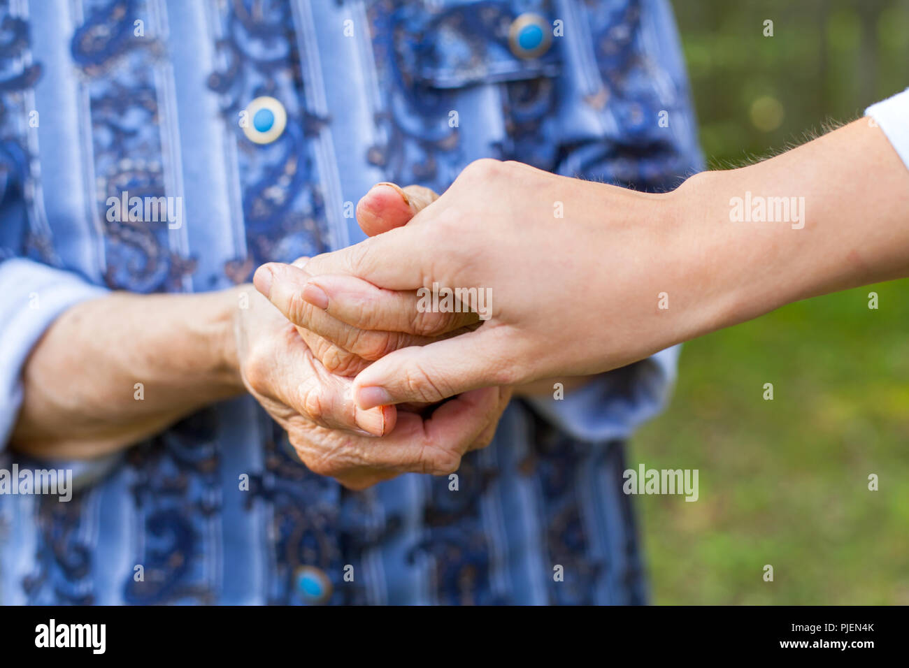 Close up picture of young woman holding her senior grandmother's wrinkled hands - Stock Image