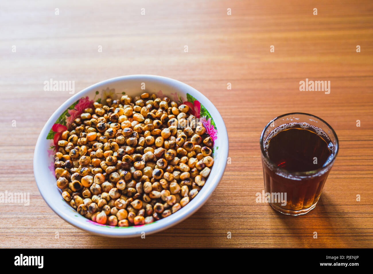 One of the most popular snacks of nepal Fried Corn with black tea on the wooden Table. - Stock Image