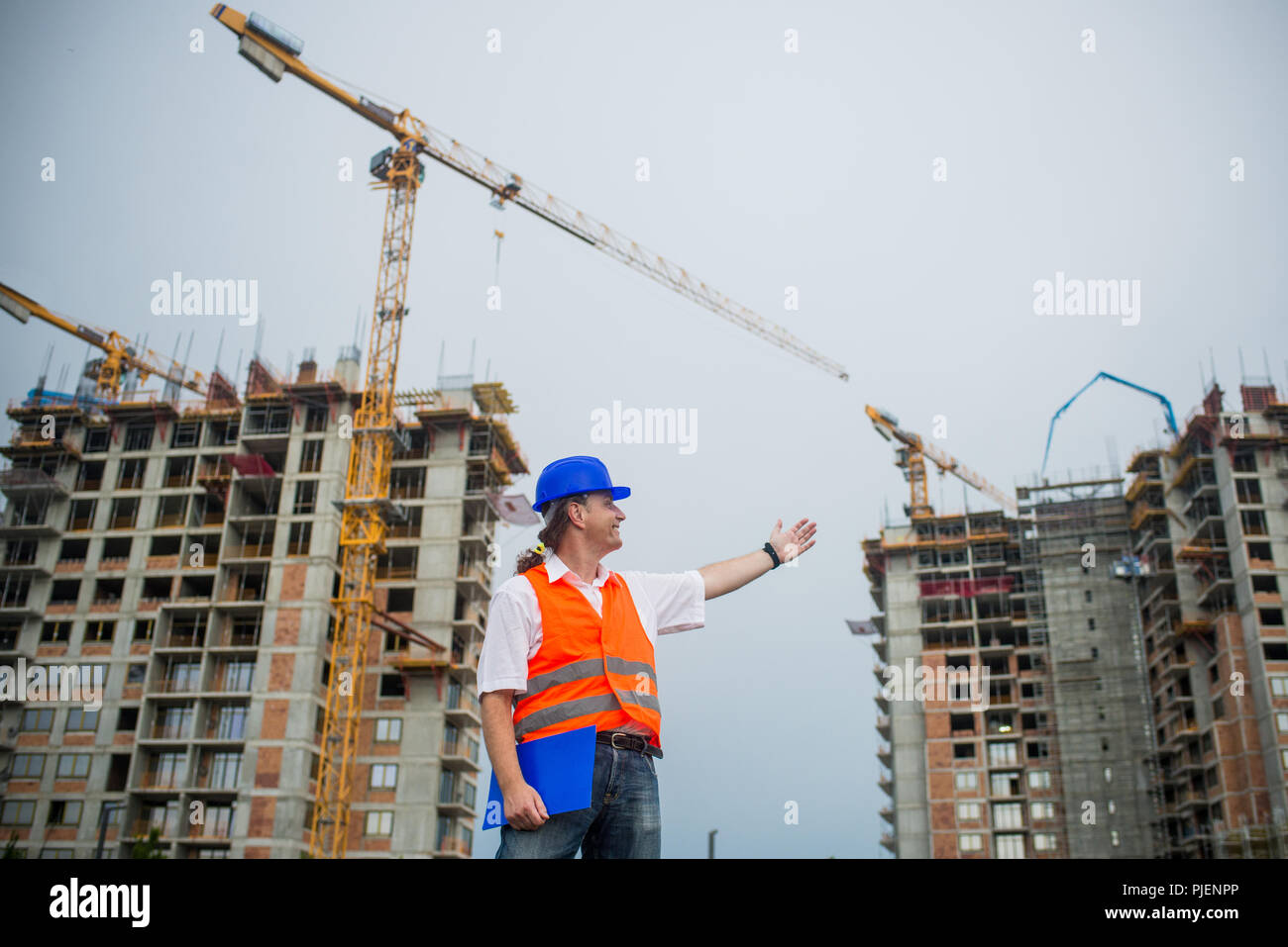 Architect showing buildings on a construction site during a housing project - Stock Image