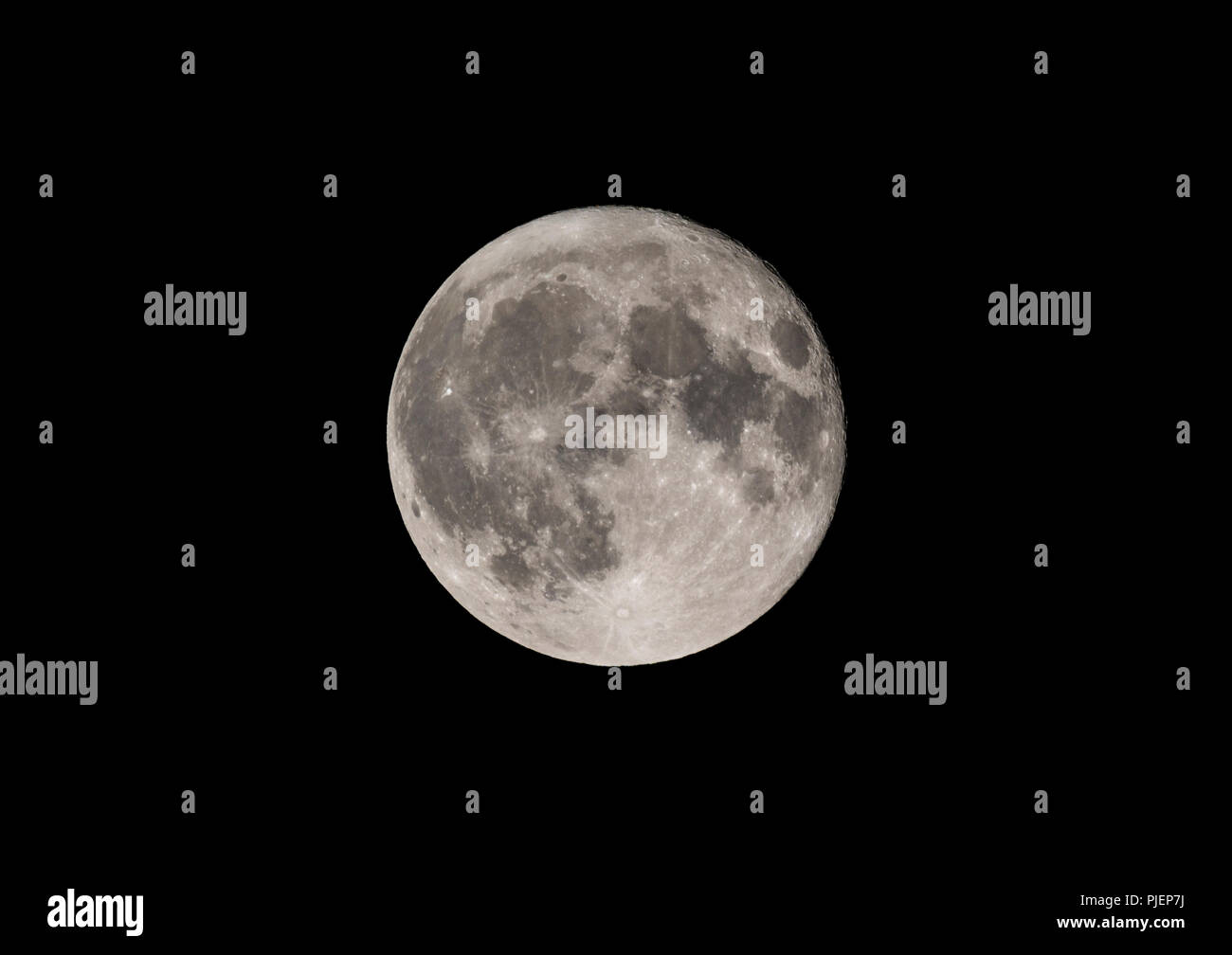 Full moon in the night sky. See description for more details of the exact phase. Stock Photo