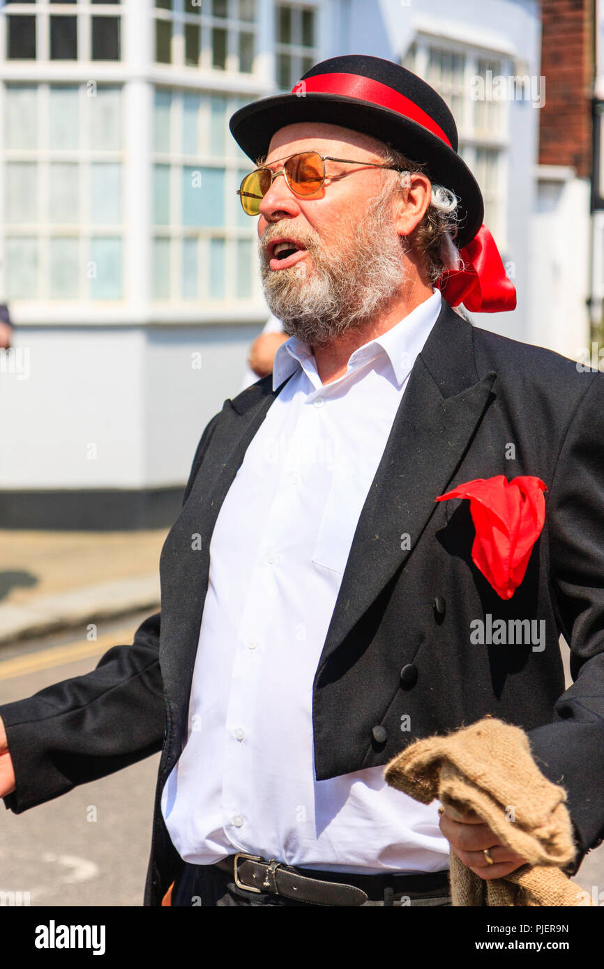 The Thameside Mummers perform a mummer play in the medieval town of Sandwich. Men dressed up in black jacket and red hankie in top pocket. - Stock Image