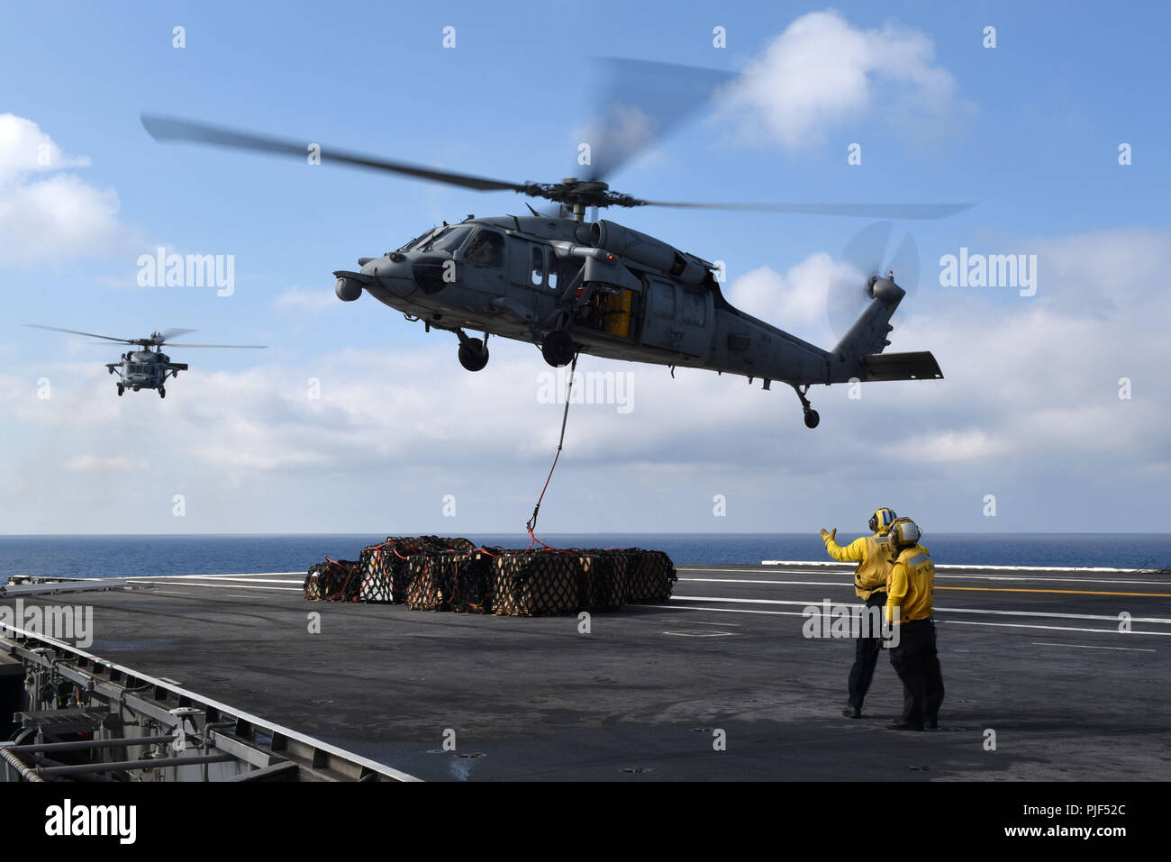 September 5, 2018 - Atlantic Ocean - ATLANTIC OCEAN (Sept. 5, 2018) Sailors direct an MH-60S Sea Hawk helicopter assigned to the Dragon Slayers of Helicopter Sea Combat Squadron (HSC) 11 on the flight deck of the Nimitz-class aircraft carrier USS Harry S. Truman (CVN 75) during a replenishment-at-sea with the fast combat support ship USNS Arctic (T-AOE-8), not pictured. Harry S. Truman is conducting sustainment operations in the Atlantic. (U.S. Navy photo by Mass Communication Specialist Seaman Maxwell Higgins/Released) 180905-N-MQ631-0271  US Navy via globallookpress.com (Credit Image: © Us N - Stock Image