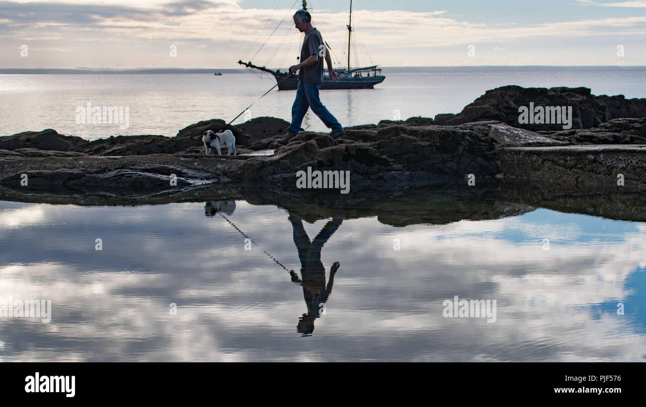 Man walking dog in the early morning on the coast round a rock pool with reflections in the pool - Stock Image