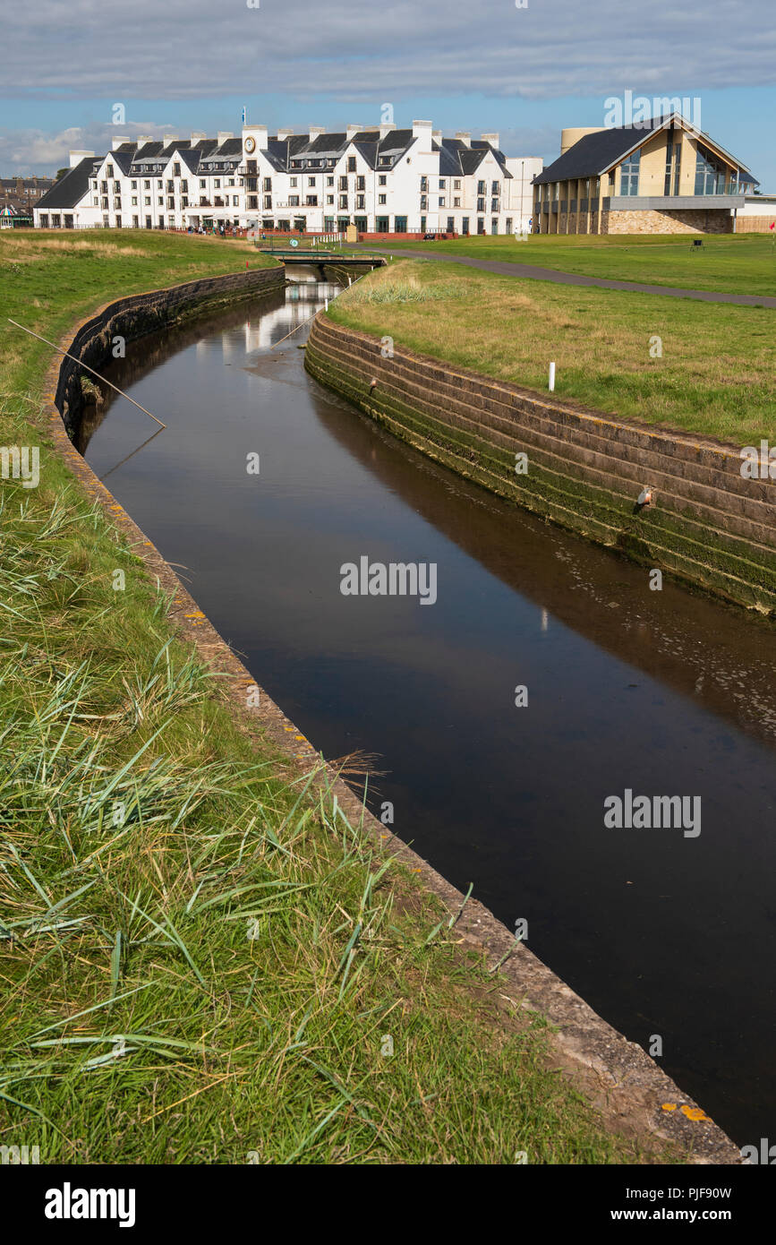 The Barry Burn meanders through Carnoustie Golf Links, with the Carnoustie Golf Hotel and Simpsons Golf Shop in the background, Carnoustie, Angus - Stock Image