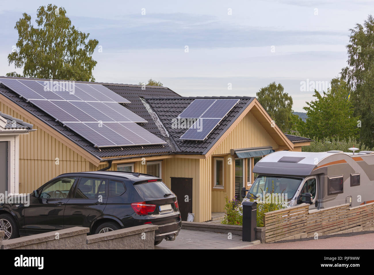 Solar panels on top of roof tiles on typical swedish or scandinavian wood panel house - Stock Image