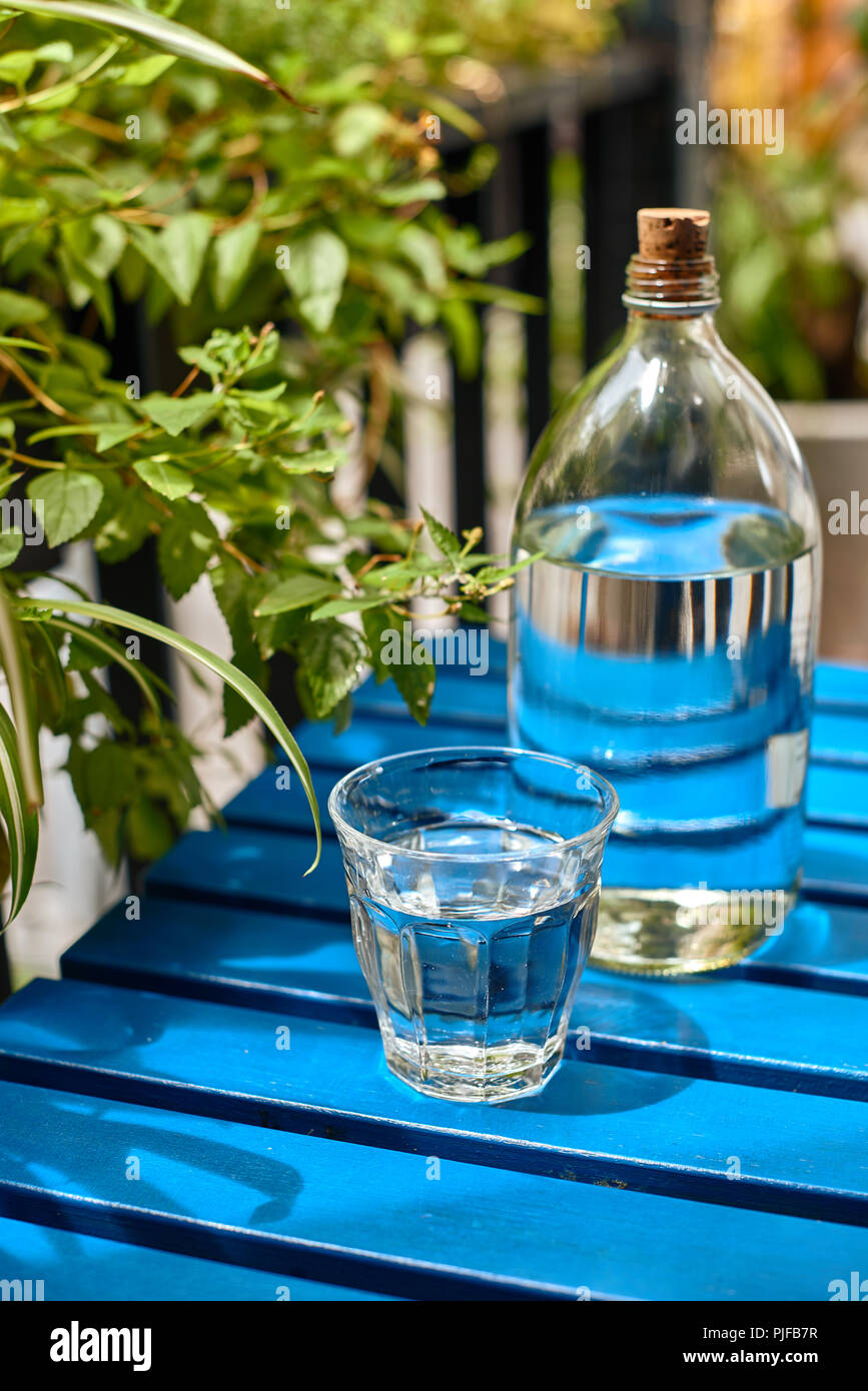The glass bottle of tap water on the blue table in the sunny day - Stock Image