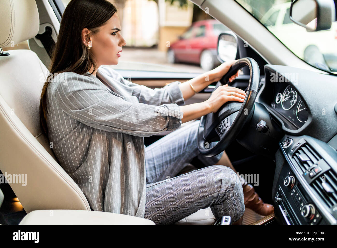 Beautiful blonde woman beep in the car in panic with closed eyes while driving on high speed. - Stock Image