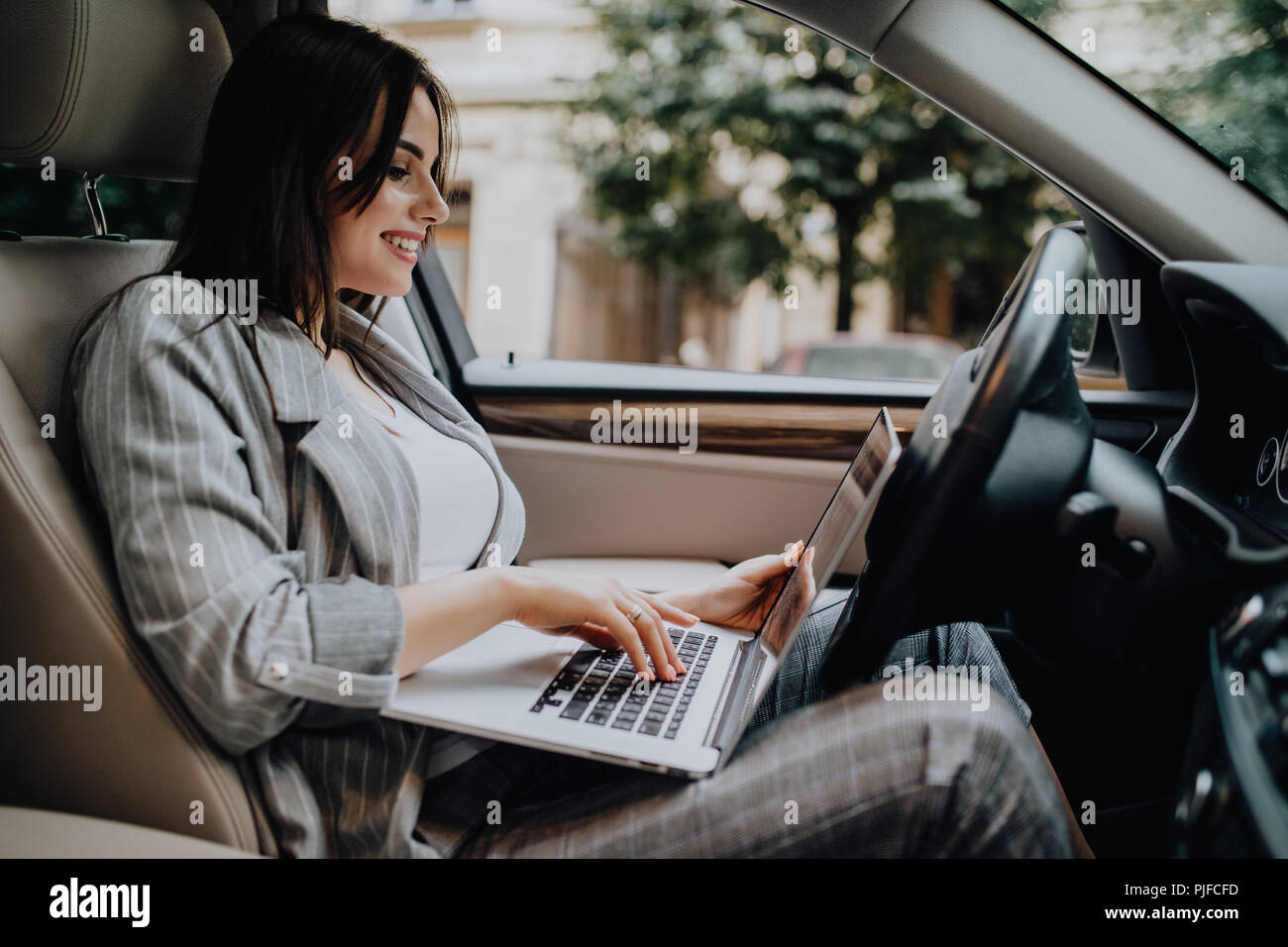 Businesswoman with a laptop in her car - Stock Image