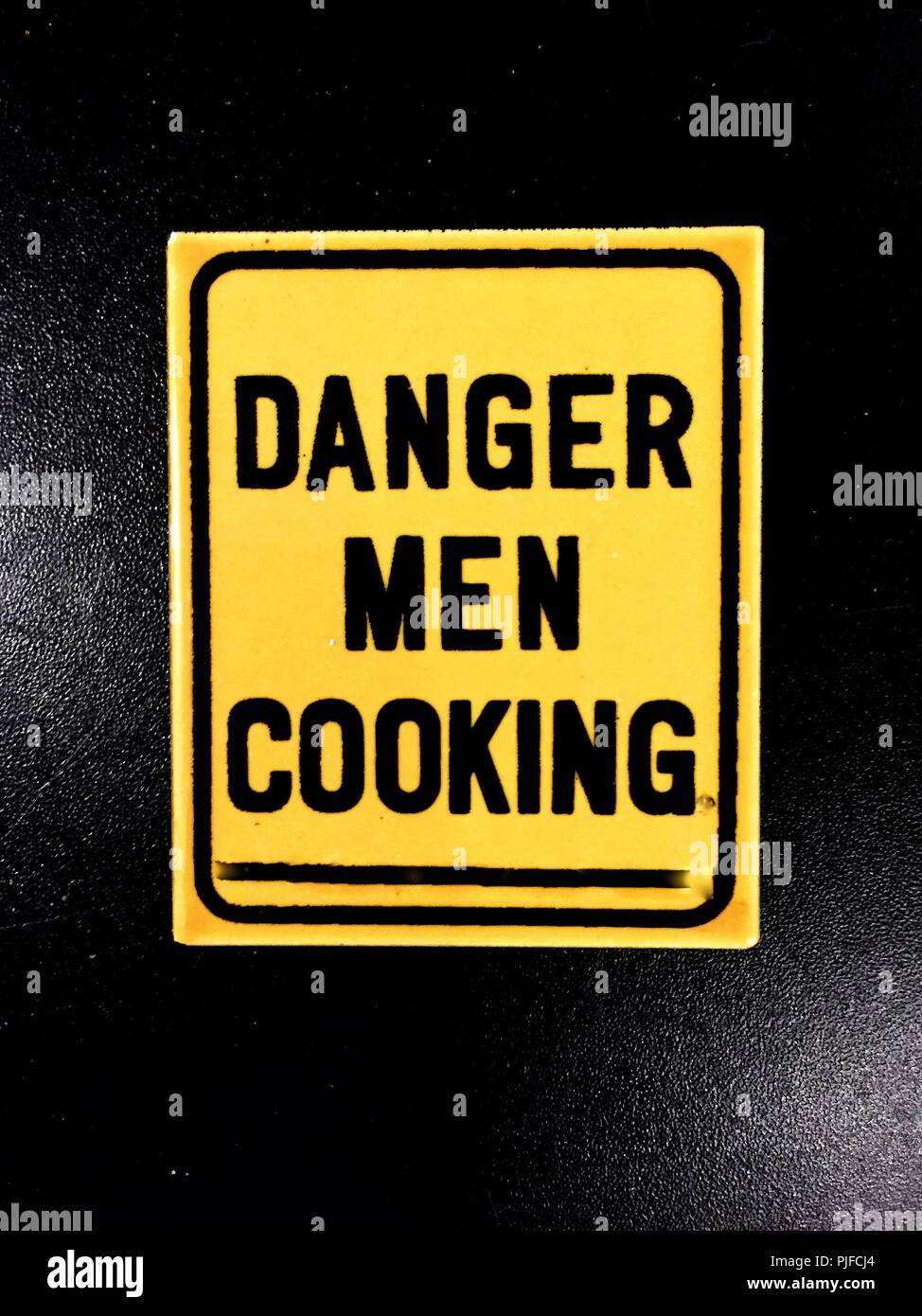 A funny fridge magnet with the words Danger Men Cooking printed on - Stock Image