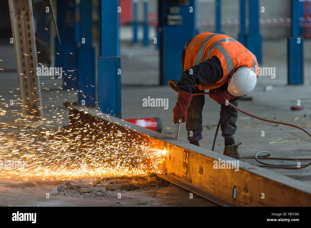 Building site worker cutting a beam with an acetylene torch - Stock Image