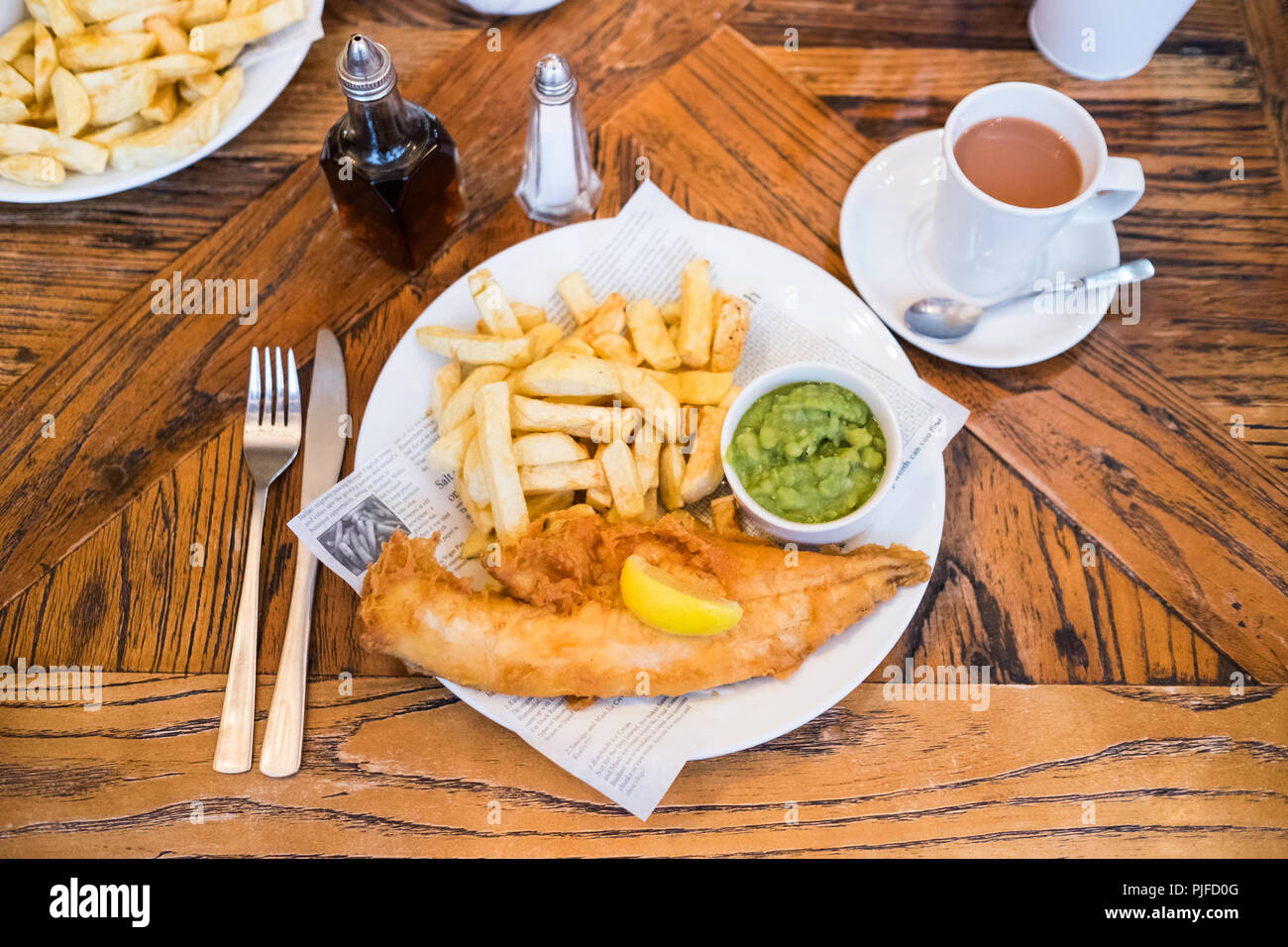 Haddock and chips with mushy peas at Lewis's Fish Restaurant, Seahouses, Northumberland, England - Stock Image