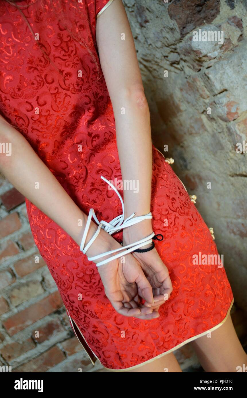 Young woman in red dress with tied hands behind her back. Indoor photo, kidnapped girl in basement, ruins. - Stock Image