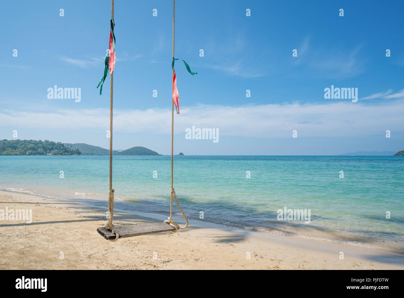 Swing hang from coconut palm tree over summer beach sea in Phuket ,Thailand. Summer, Travel, Vacation and Holiday concept - Stock Image
