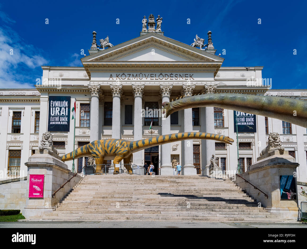 Summer sight at the Mora Ferenc Museum in Szeged. Dinosaurs models in front of the entrance of the neoclassical building. - Stock Image