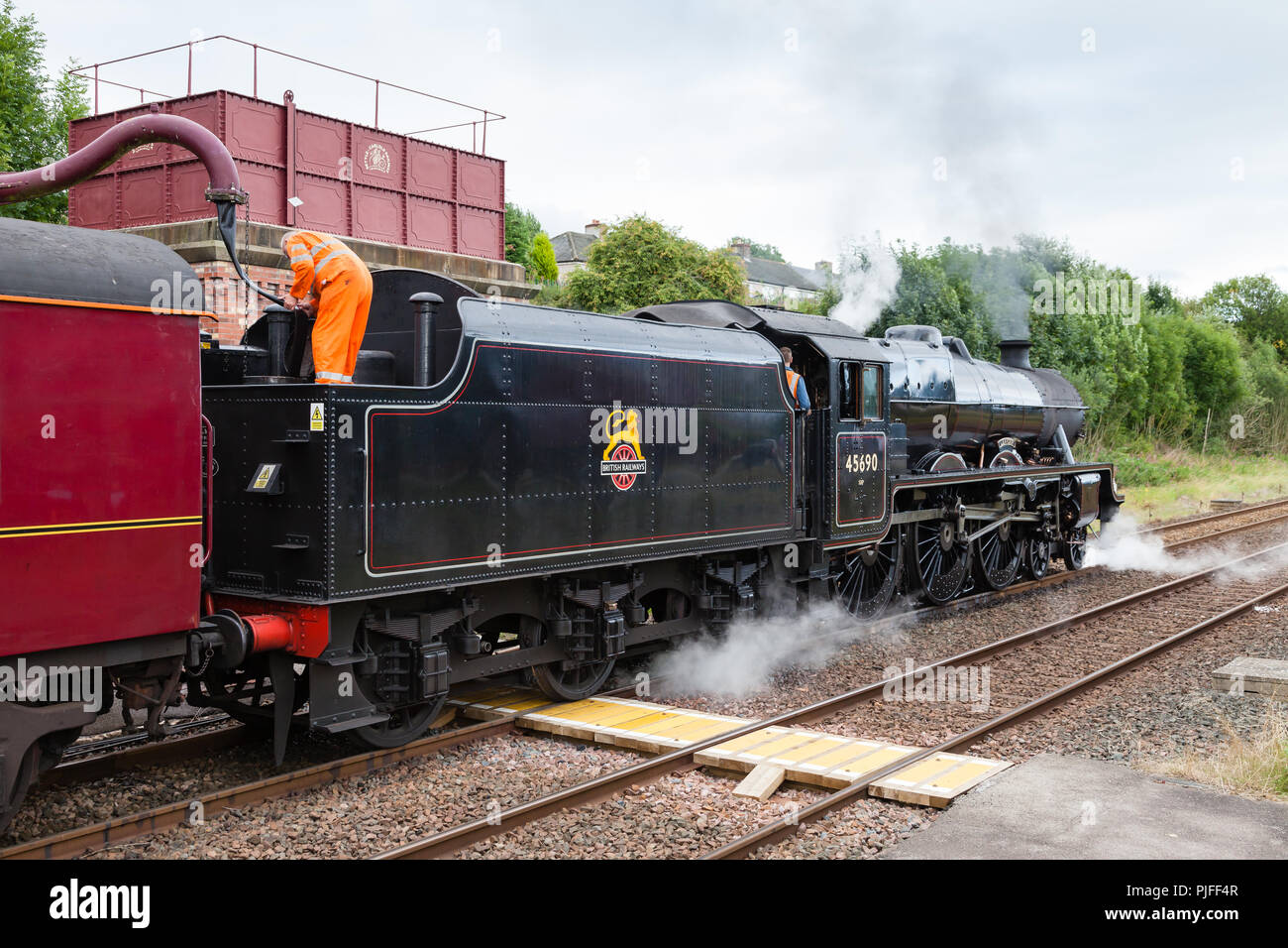 Steam train 45690, Leander, takes on water at Appleby in Cumbria, England on the Settle to Carlisle railway. - Stock Image