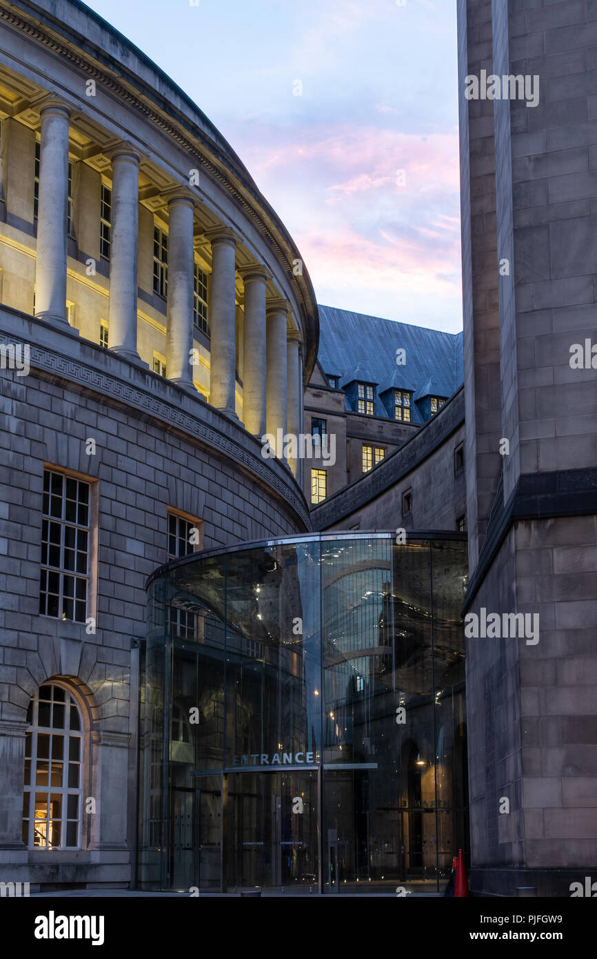 Manchester, ENgland, UK - July 1, 2018: The sun sets behind the modern entrance to Manchester's classical Central Library and Town Hall Extension buil - Stock Image