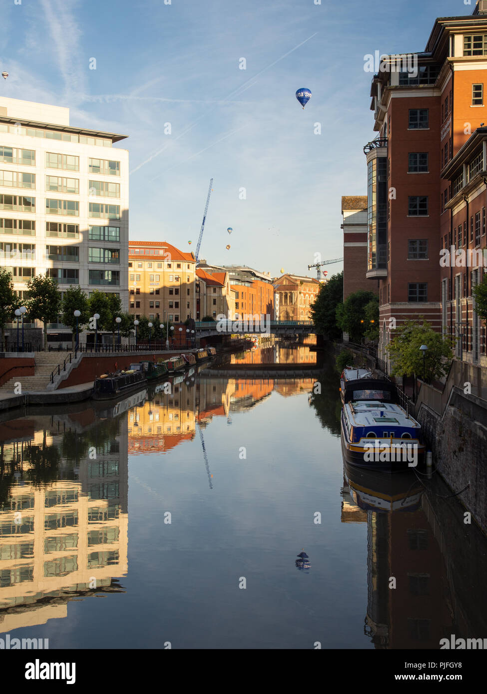 Bristol, England, UK - August 11, 2018: Hot air balloons fly above modern office buildings at Temple Quay on Bristol's Floating Harbour at dawn during - Stock Image