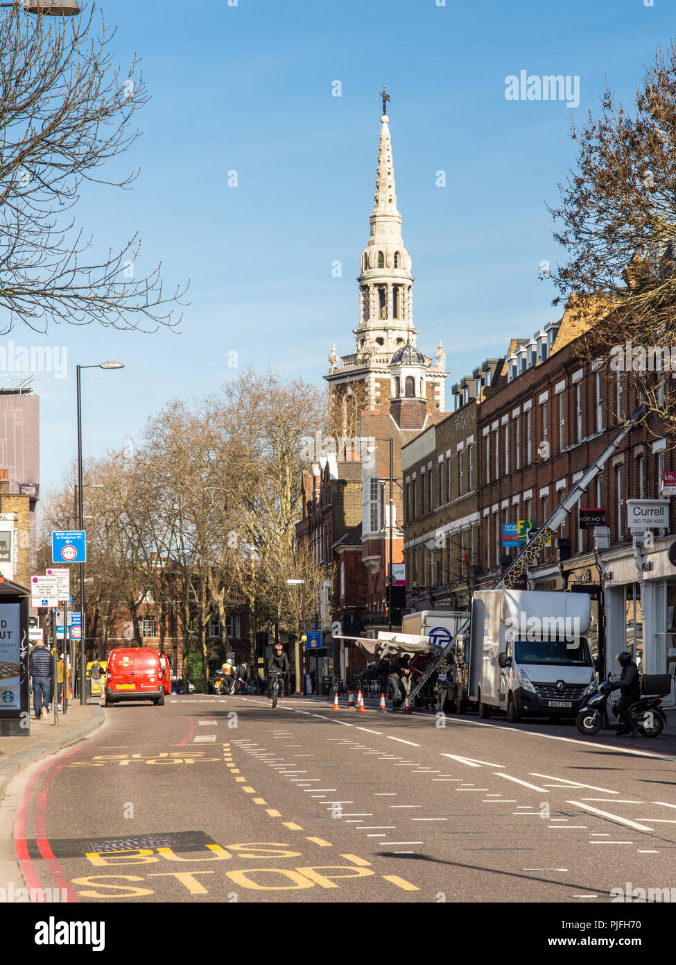 London, England, UK - February 12, 2018: Deliveries are made to shops and houses along the main Upper Street through Islington, London, with the spire - Stock Image