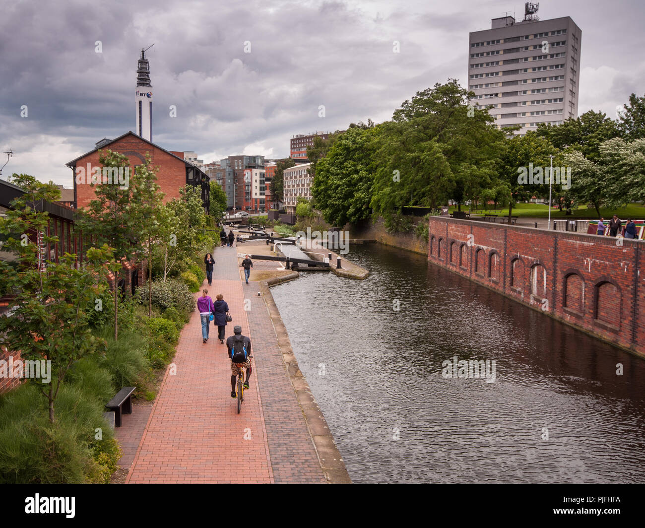 Birmingham, England, UK - June 23, 2012: Cyclists and pedestrians travel on the towpath alongside the Grand Union Canal in Birmingham city centre, wit - Stock Image