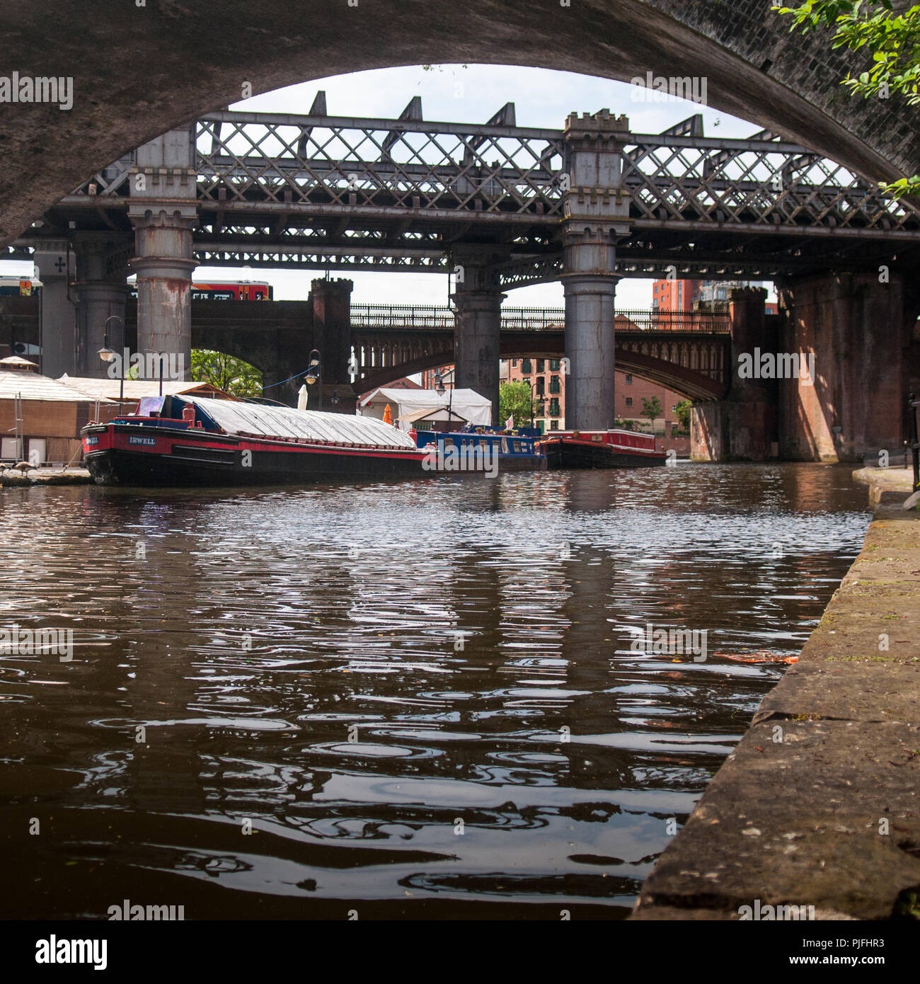 Manchester, England, UK - May 21, 2011: An East Midlands Trains passenger train crosses Castlefield basin on the Bridgewater Canal in Manchester. - Stock Image